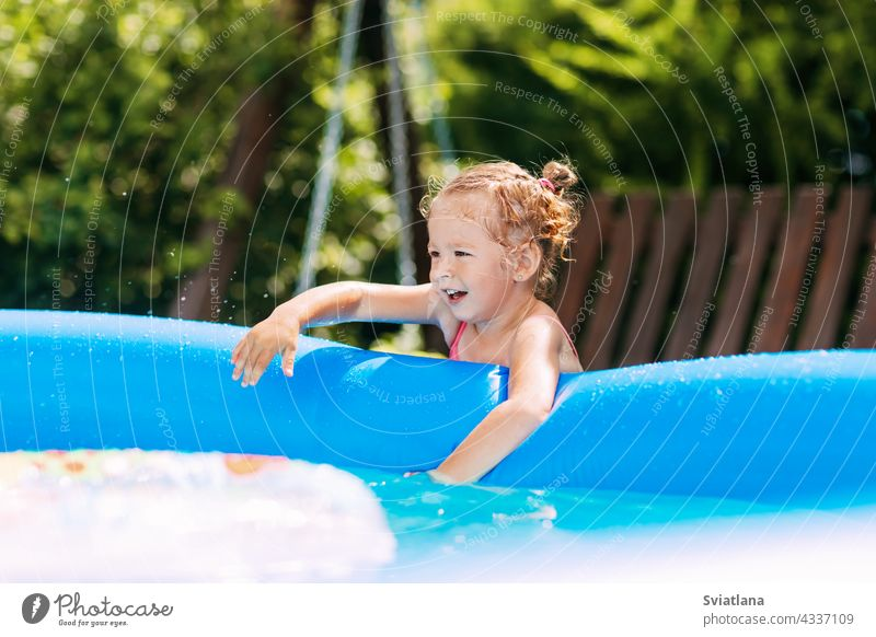 A charming baby touches the water in an inflatable pool in the garden and smiles girl playing fun childhood summer kid swimming joy swimsuit family funny little