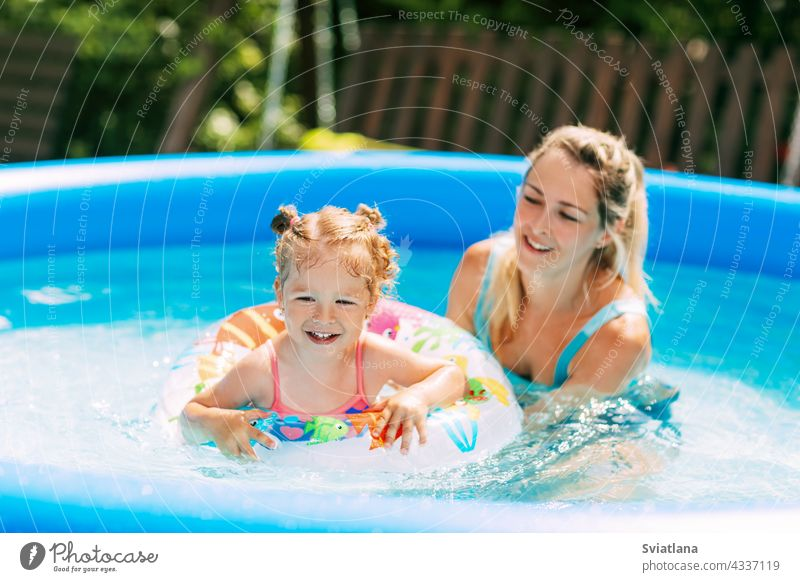 A young mother teaches her little daughter to swim in the pool in the garden with the help of an inflatable circle mom swimsuit water childhood cheerful weekend