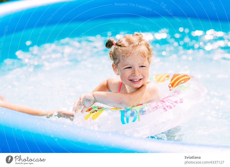 A laughing baby in a bright swimsuit learns to swim in the pool in the garden with the help of an inflatable circle. Summer time, recreation, rear view girl