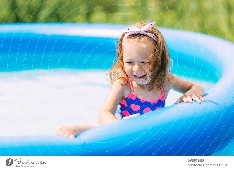 Portrait of a beautiful baby girl in the pool in the garden water playing fun childhood summer kid swimming joy swimsuit family funny little vacation sun