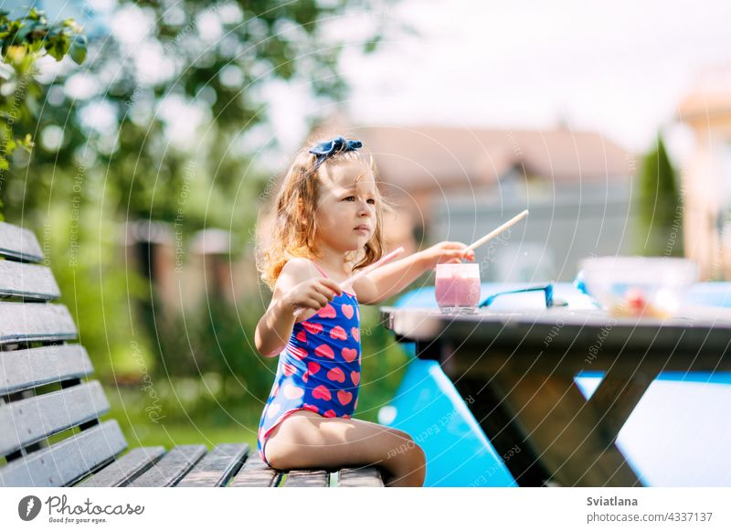 A cute baby is drinking a berry smoothie through a straw, sitting on a bench in the garden. Outdoor recreation, summer holidays for children healthy vitamin