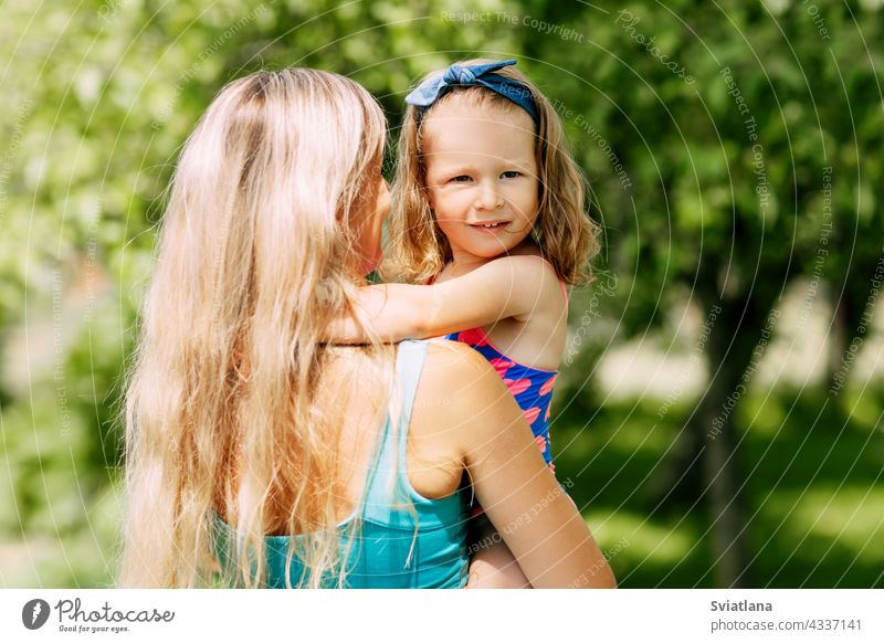A young mother holds her little daughter in her arms on a summer day in the garden or park family parent mom child childhood happy togetherness motherhood care