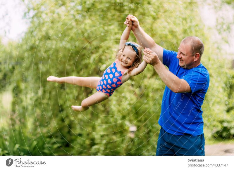 A cute father and a little girl are playing together. The child takes off in the hands of his father baby flying daughter man park family day love happy dad