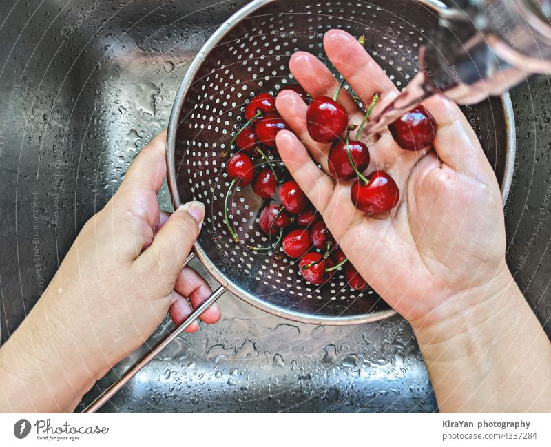 Ripe fresh cherries berry in steel sieve is hand washed under tap water in sink fruit summer cooking top view kitchen woman vibes ripe pov hand washing metal
