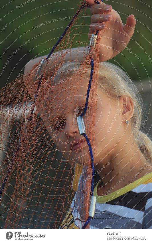 Portrait of a blond teenage girl through a fishing net. A blond girl holding a fishing tackle in front of her face outdoors. blonde fishnet teenager portrait