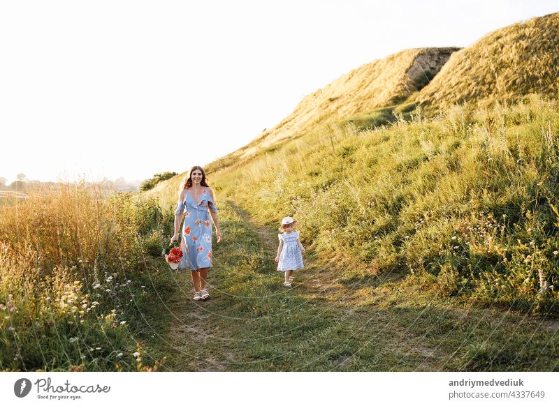 Young mother walking with her little daughter in the green field. Family holiday in garden. Portrait mom with child together on nature. Mum, little daughter outdoors. Happy Mothers Day. Close up.