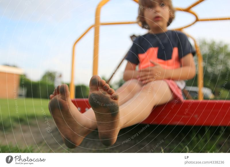 boy sitting down showing dirty feet at the camera Education Religion and faith Connection Innocent Playful Meditation Senses Calm Background picture