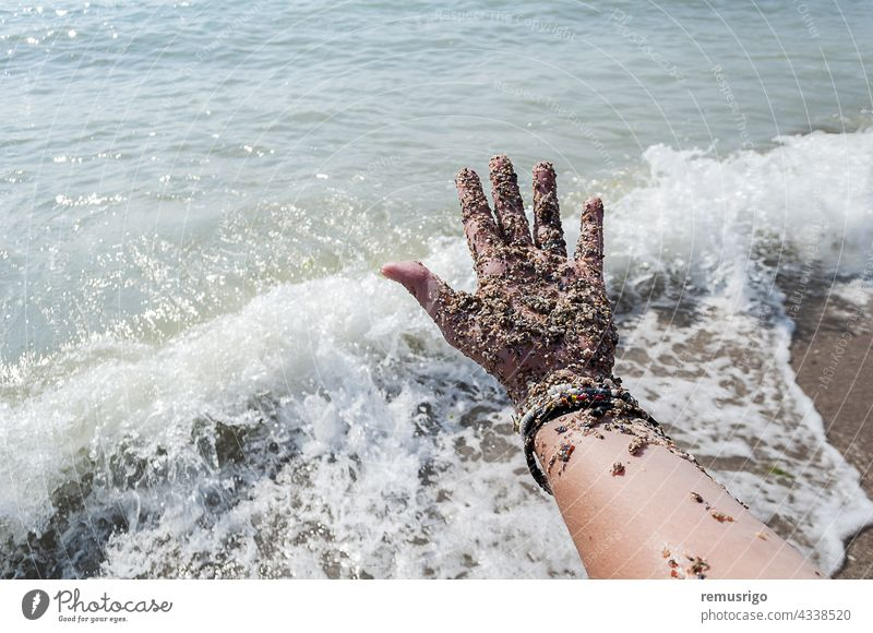 Hand covered with sand adult beach body bracelet caucasian coastline female fingers foam hand holiday human island nature ocean outdoors part people person sea