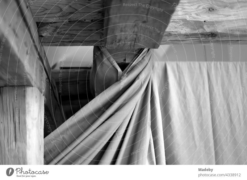 Massive old wooden roof beams under the roof and a curtain with folds in a renovated farmhouse on a farm in Rudersau near Rottenbuch in Upper Bavaria, photographed in traditional black and white