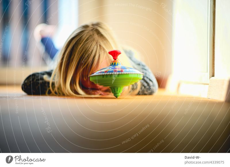 Child playing in a top Playing Girl Toys self-employment Gyroscope Rotate Joy Infancy Enthusiasm Cute floor