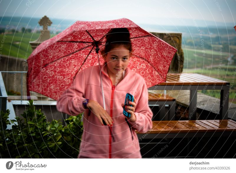 Everything in pink. Young girl stands with umbrella and rain jacket in the outdoor area of the restaurant.  The mobile phone in hand and looks desperately to the photographer, when is he finally ready .