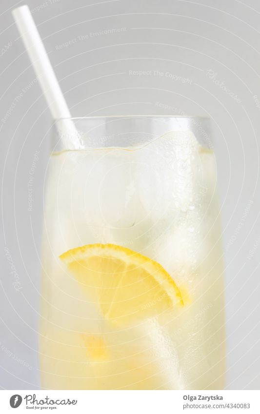 Glass of lemonade. drink cold water ice glass straw paper summer refreshment close up citrus perspiration beverage gray minimal cocktail background cool