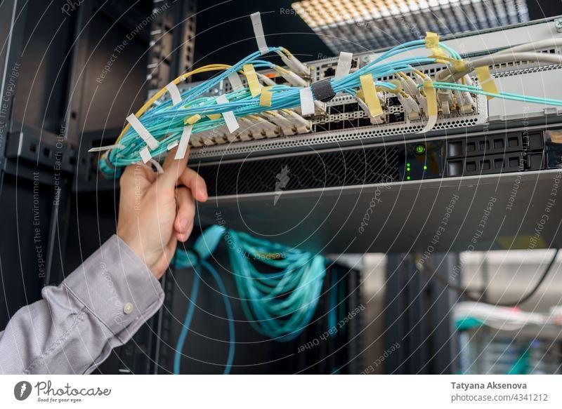 Man data center technician performing server maintenance infrastructure engineer rack cables replacing blade mounted fiber optics rj45 recovery man working it