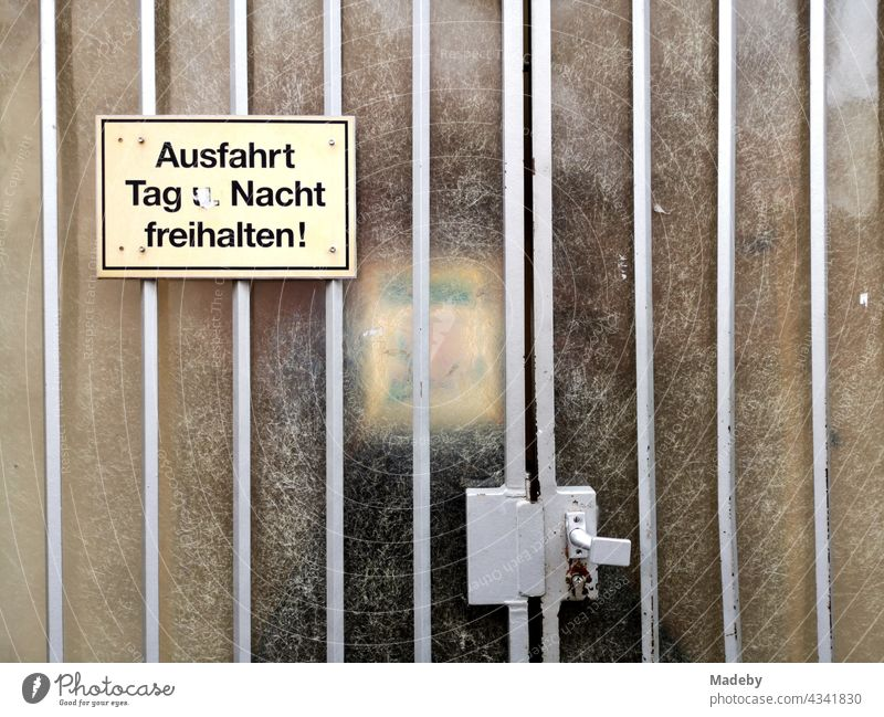 Yellow plastic sign on an old gate with rippled glass in front of a courtyard entrance in Offenbach am Main in Hesse plastic shield Yellowed interdiction Warn