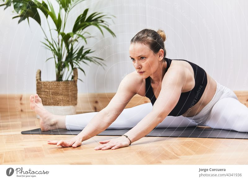 partial detail of Russian woman practicing yoga nood on a mat female exercise pilates body girl training hair stretching yogi young adult aerobics asana balance