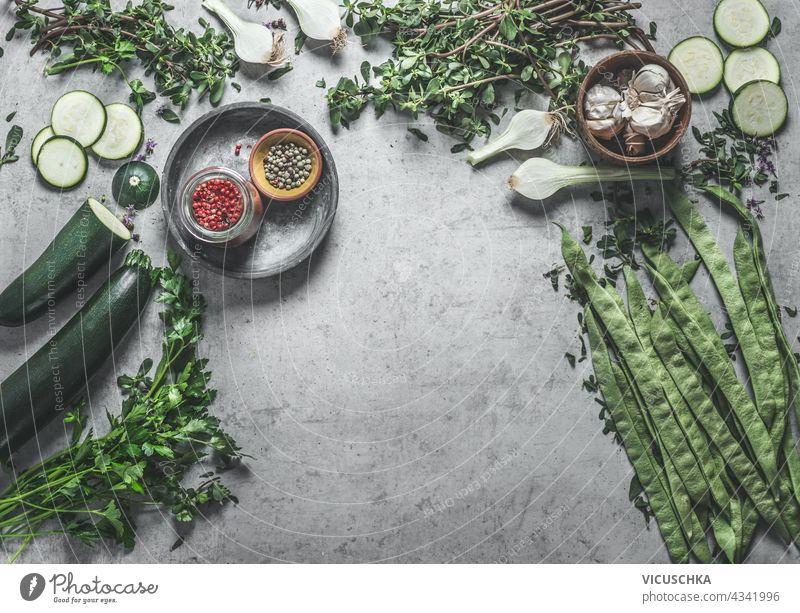 Various healthy green vegetables and herbs ingredients on concrete kitchen table background. Top view. Home cooking. Vegan food various top view home vegan food
