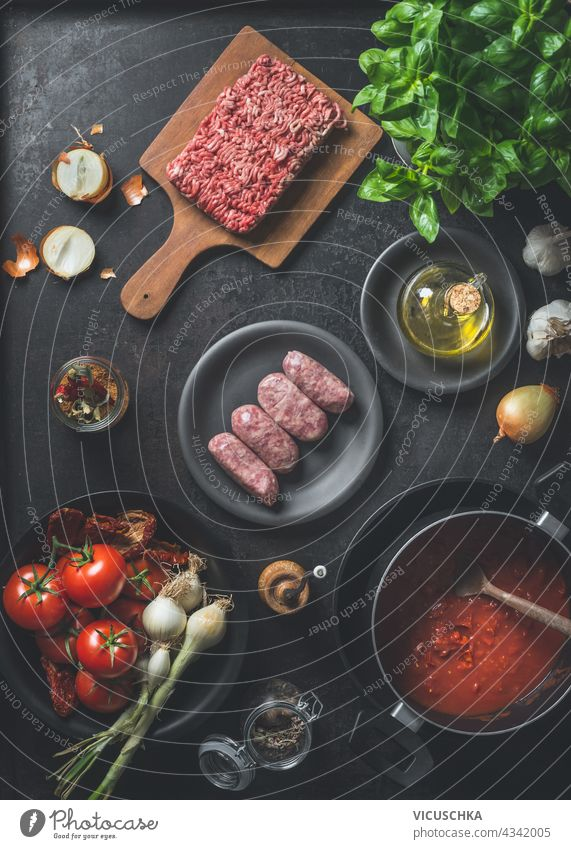 Various ingredients for Sauce bolognese : Salsiccia sausages, minced meat, tomatoes sauce, herbs and spices on dark kitchen background. Top view. Cooking preparation