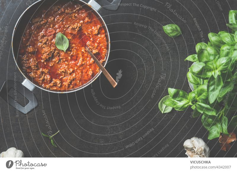 Food background with sauce bolognese in black cooking pot on dark background. Top view food top view tomato sauce bolognese sauce saucepan minced cooked