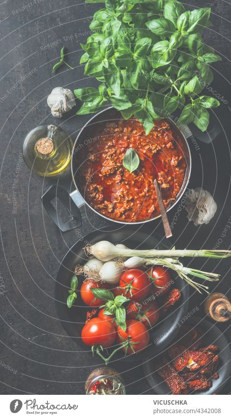 Sauce bolognese in black cooking pot on dark kitchen table background with ingredients. Top view sauce top view homemade bolognese ingredient traditional
