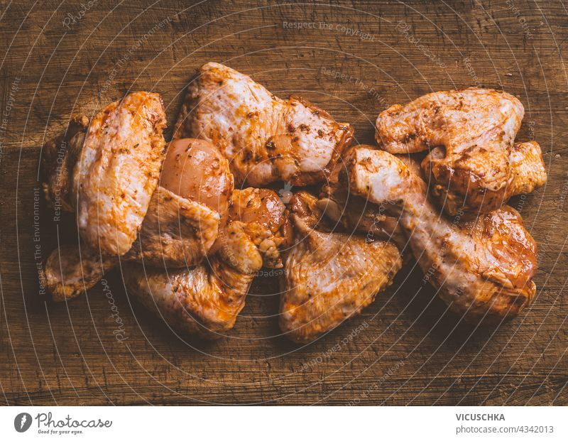 Marinated chicken pieces for grill or roasting on wooden background. Top view marinated top vie top view poultry hot roasted wings sauce delicious tasty cuisine