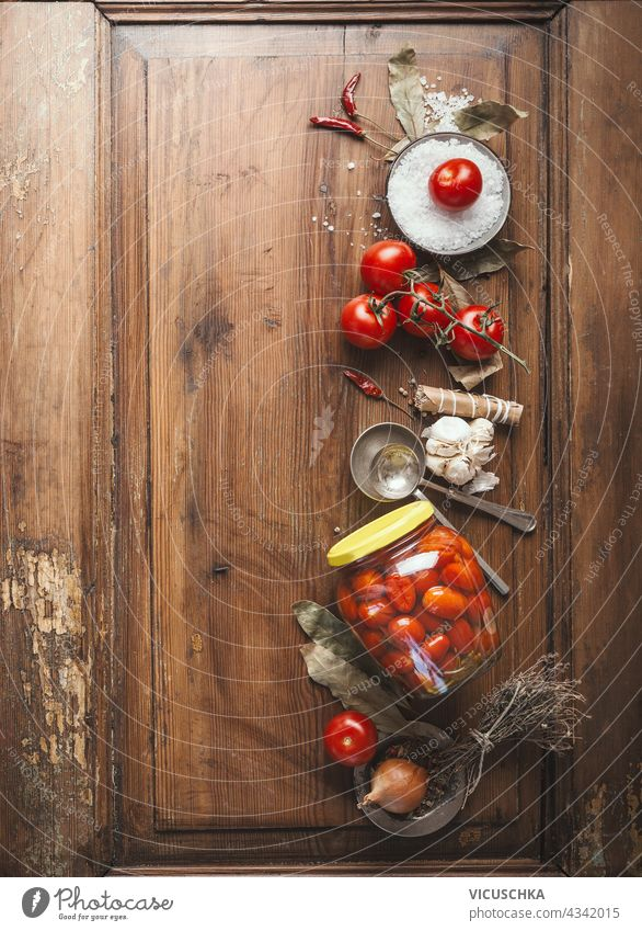 Tomatoes preserving.  Jar with fermented tomatoes on wooden table background with ingredients. Top view jar top view nobody natural traditional pickled