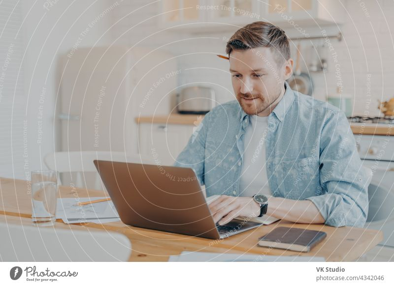 Focused young man freelancer using laptop while sitting at kitchen table working remotely home data handsome smile indoors male business computer casual typing