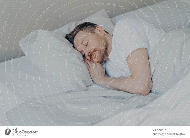 Handsome young man comfortably sleeping in bed at home nap happy handsome bedroom cozy comfortable bedding relax peaceful asleep indoors lying lifestyle pillow