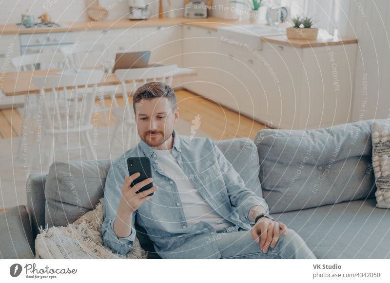 Attractive caucasian young man in domestic casual clothes using smartphone at home bearded cheerful mobile smiling sofa person positivity rest resting surfing