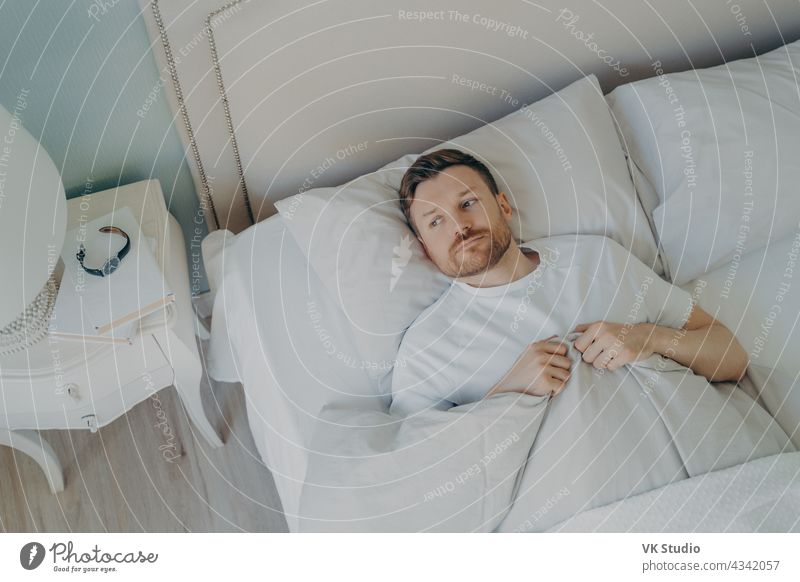Handsome stressed young caucasian male lying in bed with his eyes open man sleep bedroom insomnia tired restless pillow indoor home adult worried awake bedtime