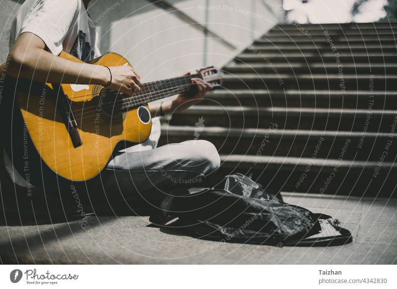 Street performer plays guitar .  Young street musician playing guitar and busking for money artist musical player sound instrument male string acoustic man rock