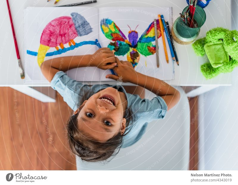 Top view of a girl painting at home on the table happy playful female children young happiness person art paper inspiration little education kindergarten