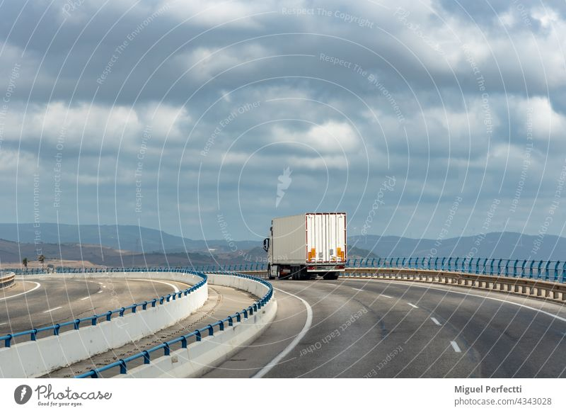 Truck with metal semi-trailer, widely used in textile and automotive industry, driving over bridge with cloudy sky. Trailer Street Transport Highway Cargo
