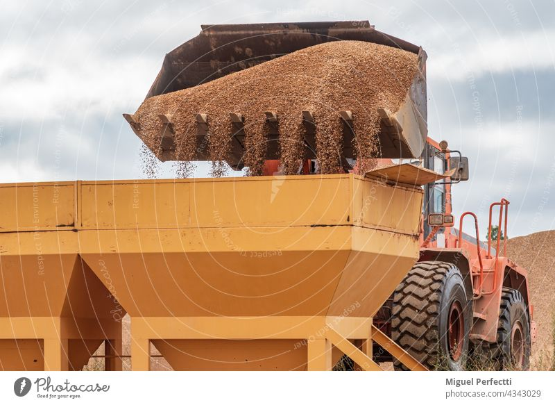 Bucket of an excavator pouring sand into silos. excavator shovel digger machine construction industry industrial architecture quarry old metal steel work iron