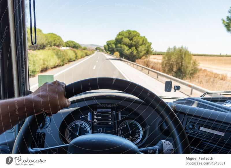View that a truck driver has from his workplace, with one hand gripping the steering wheel, the dashboard with job information and the road in the background.