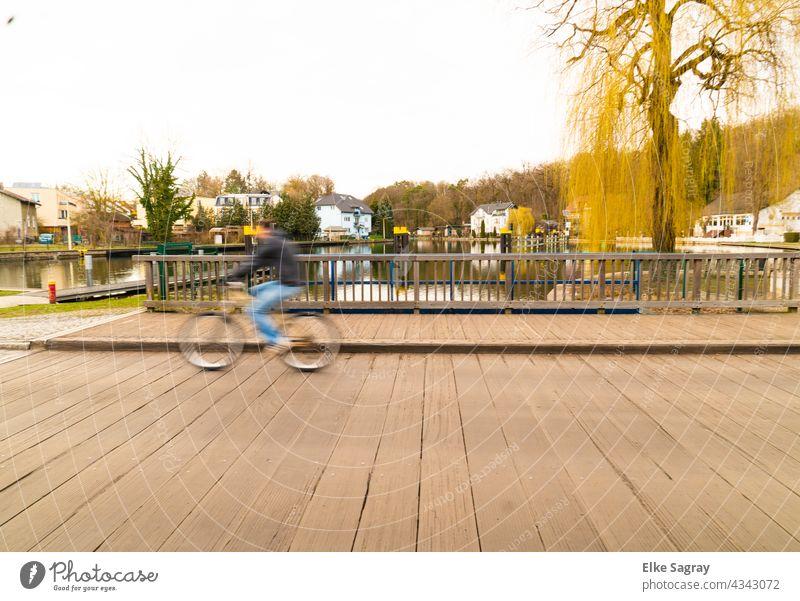 INCREDIBLE speeding cyclist rolls over bridge Bridge blurred hazy cyclists blurriness Abstract Light Colour urban Street bokeh Outdoors defocused people swift