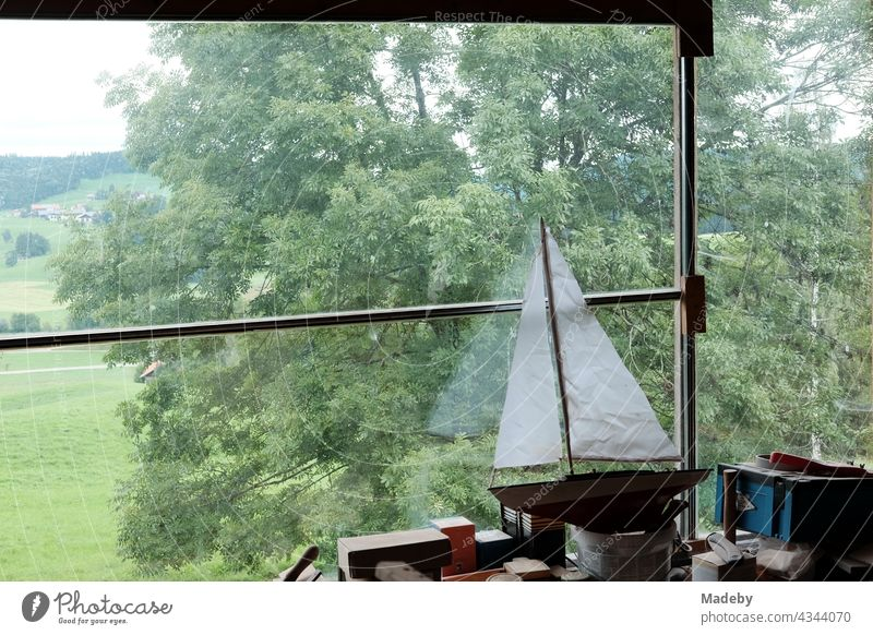 Beautiful wooden model of a sailing yacht with white sails on the workbench in a converted old barn with panorama window on a farm in Rudersau near Rottenbuch in the district of Weilheim-Schongau in Upper Bavaria