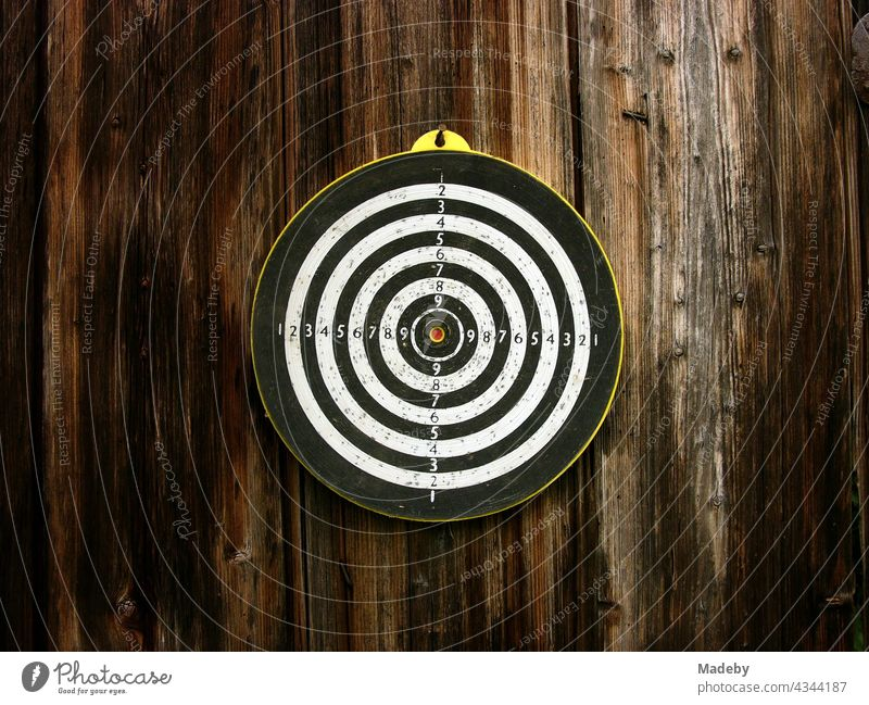 Old round target for the dart game with arrows on the brown wood of an old barn in Rudersau near Rottenbuch in the district Weilheim-Schongau in Upper Bavaria