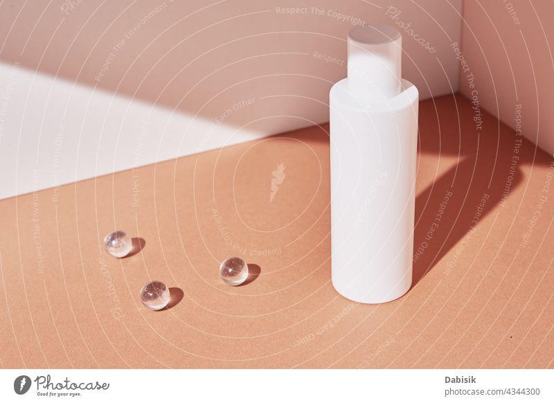 Natural cosmetic product. White bottle on pastel background cosmetics cream skin care mockup serum design minimal geometric shape shadow composition beige