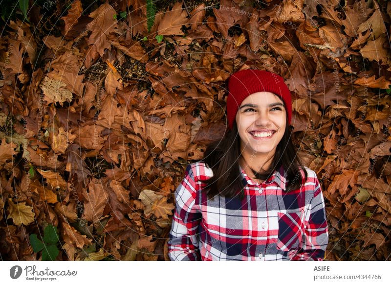 Laughing teen girl lying in a bed of dry leaves in autumn happy smile laughing joy fun positive cheerful copy space eyes toothy dreamer fall playful funny cute