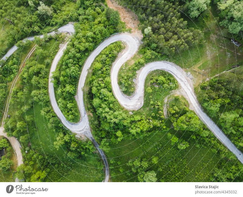 Drone view of beautiful serpentine road leading through mountain landscape in summer.  Aerial photography of a road shot using a drone.  Damaged road surface