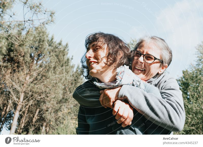 Senior woman and her daughter smiling and having fun on the forest during a sunny day. Happy mother's day joy laughing togetherness happiness people care face