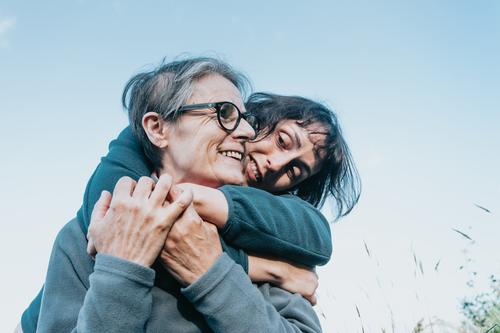 Senior woman and her daughter smiling and having fun on the nature during a sunny day. Happy mother's day joy laughing togetherness happiness people care face