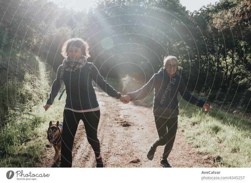 Senior woman and her daughter smiling and having fun on the forest during a sunny day. Running together with their dog, Happy mother's day joy laughing