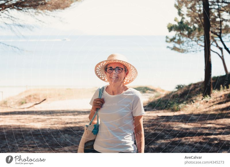 oman with gray hair at the beach during a super sunny day, senior freedom concept, copy space, relax and mental health person woman elderly retired retirement