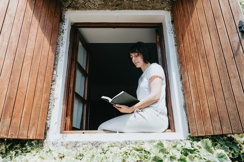 A young female with a book sitting on window sill, reading and relaxing during a sunny day teenage person education indoor room school student studying happy