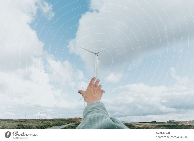 Human hand reaching Wind Turbines Windmill Energy on the nature, during a super sunny day, with copy space and a lot of air electricity power renewable turbine