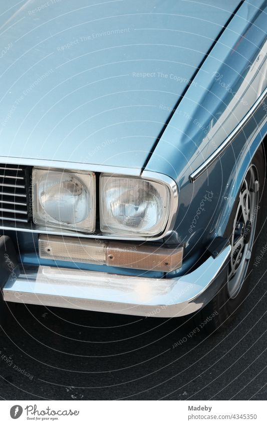 Angular double headlights of a blue french sedan of the seventies with shining chrome in the sunshine at the Golden Oldies in Wettenberg Krofdorf-Gleiberg near Giessen in Hesse