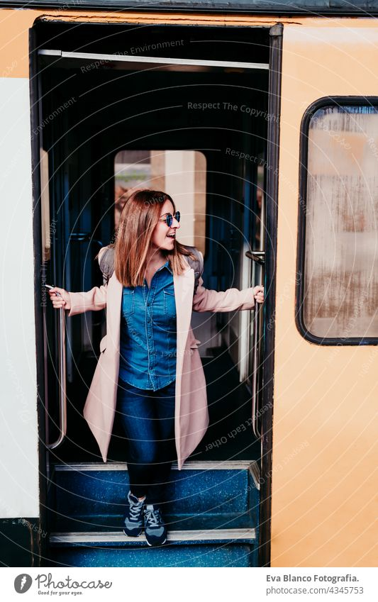 smiling young backpacker caucasian woman standing on wagon at train station. Travel concept mobile phone travel happy technology daytime Porto platform arrival