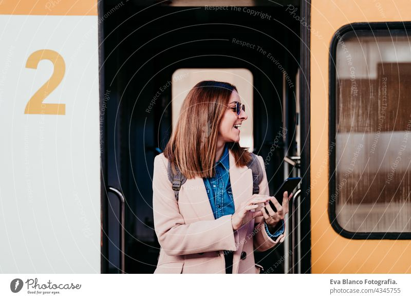 young backpacker caucasian woman at train station using mobile phone. Travel concept travel happy technology daytime Porto platform arrival baggage beautiful