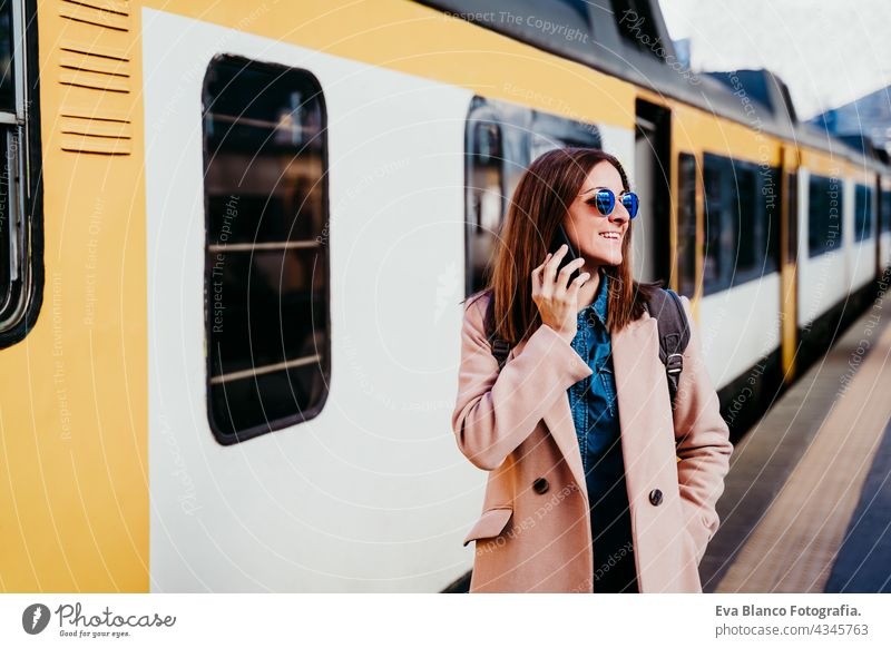 happy backpacker caucasian woman at platform on train station talking on mobile phone. Travel concept travel technology daytime Porto arrival baggage beautiful